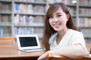 schöne asiatische Studentin mit Laptop für das Studium in der Bibliothek foto