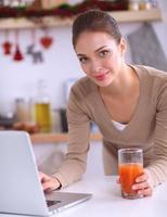 Frau mit einem Laptop beim Trinken von Saft in ihrer Küche