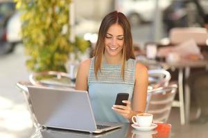 Unternehmer, der mit einem Telefon und einem Laptop im Café arbeitet