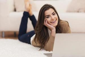 glückliche Frau, die auf Teppich mit Laptop liegt