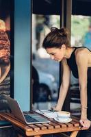 attraktive Geschäftsfrau, die an seinem Laptop arbeitet