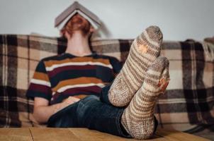 junger Mann, der mit Buch auf Kutsche in löchrigen Socken schläft foto