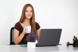 Porträt der jungen Geschäftsfrau, die in ihrem Büro arbeitet.