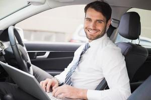 Geschäftsmann, der auf dem Fahrersitz arbeitet foto