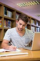 Student studiert in der Bibliothek mit Laptop