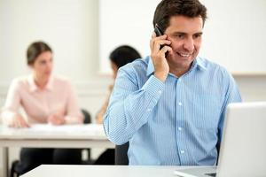 Executive Latin Mann im Gespräch auf seinem Handy foto
