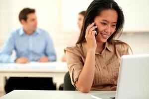 asiatische Geschäftsfrau spricht auf ihrem Handy foto