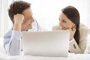 glückliches Geschäftspaar mit Laptop, der einander ansieht foto