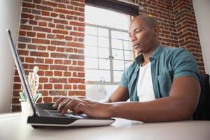 Gelegenheitsgeschäftsmann, der am Laptop am Schreibtisch arbeitet