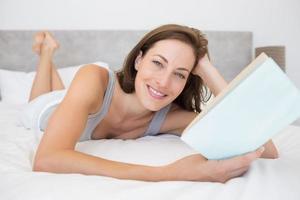 ziemlich entspannte Frau, die Buch im Bett liest