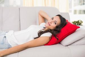 hübsche Brünette, die sich auf der Couch entspannt