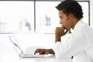 Geschäftsmann sitzt am Schreibtisch im Büro foto