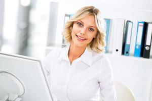 Geschäftsfrau, die Computer im Büro benutzt foto