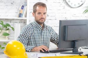 junger Ingenieur, der an seinem Computer arbeitet foto