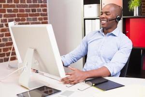 fröhlicher Geschäftsmann, der Computer im Büro benutzt foto