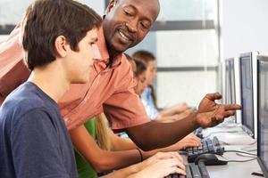 Lehrer und Schüler sitzen am Computer foto