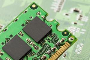 grüne Leiterplatte mit Mikrochips und Transistoren foto
