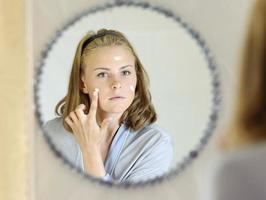 schöne junge Frau, die Gesichtscreme aufträgt foto