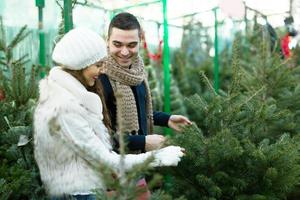 lächelndes Mädchen mit Freund am Tannenbaummarkt