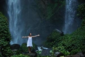 Frau meditiert Yoga zwischen Wasserfällen foto