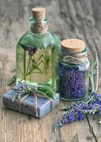 Lavendelöl, Kräuterseife und Badesalz mit Blumen foto