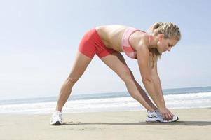 Frau, die sich am Strand aufwärmt foto