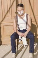 gutaussehender Mann mit Rasierschaum im Gesicht und Handtuch foto