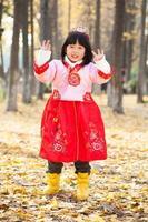 kleines Mädchenkleid im schneeweißen Kostüm im Wald foto