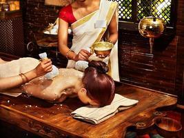 Frau, die Massage mit Reisbeutel hat. foto