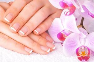 schöne Maniküre mit rosa Orchidee auf dem Weiß