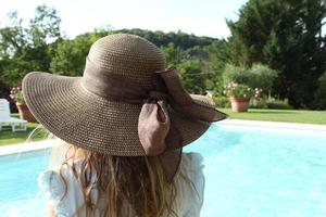 Mädchen von hinten trägt Hut und schaut einen Pool