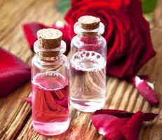 Rosenessenzflaschen mit Blütenblättern foto