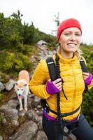 Frau, die in den Bergen mit Akita-Hund wandert