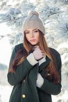 schönes Winterporträt der jungen Frau in der verschneiten Landschaft foto