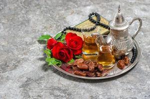 Tee, Dattelfrüchte, rote Rosenblüte foto
