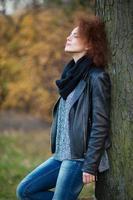 Frau, die sich auf den Baum im Freien stützt foto