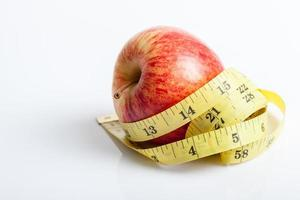 gelbes Maßband mit rotem Apfel foto