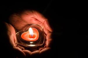 brennende Kerze in Händen foto