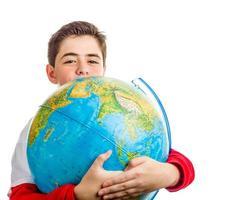 kaukasischer Junge umarmt Globus foto