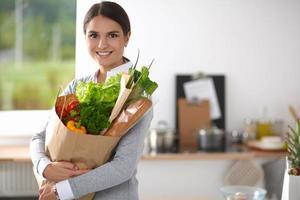 junge Frau, die Einkaufstasche des Lebensmittels mit Gemüse hält in