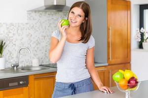 fröhlich fit Frau mit grünem Apfel