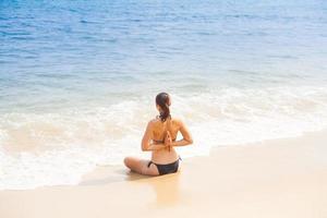 kaukasische Frau, die Yoga am Strand praktiziert foto