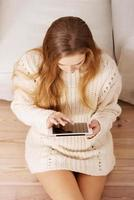 schöne kaukasische Frau, die auf Tablette spielt.