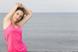 kaukasische Fitnessfrau, die ihren Trizeps streckt foto