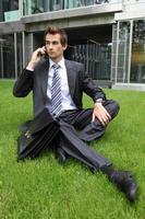 junger kaukasischer Geschäftsmann, der auf Gras sitzt foto