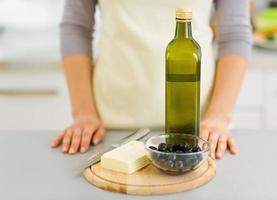 Käse, Oliven und Olivenöl auf Schneidebrett. Nahansicht