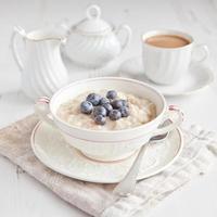 gesundes Frühstück: Haferbrei mit Kaffee auf dem Tisch