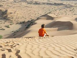 kaukasischer Junge, der auf Sanddünenrückansicht sitzt foto