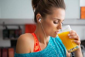 Porträt der Fitnessfrau, die Kürbis-Smoothie in der Küche trinkt foto