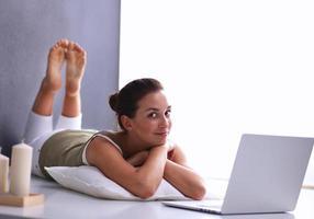 attraktives kaukasisches Mädchen, das auf Boden mit Laptop liegt foto